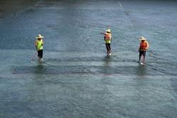 PUTRAJAYA, MALAYSIA - NOV 17: Unidentified labourers are cleaning the floor of the Putrajaya Dam on November17, 2009 in Putrajaya, Malaysia