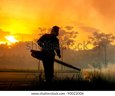 PUTRAJAYA, MALAYSIA - NOV. 27:Unidentified man is implementing fogging for dengue preventive at early morning on November 27, 2011 in Putrajaya, Malaysia. Fogging is one of requirement to kill the Aedes mosquito.