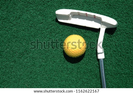 Putter laying on the green with a yellow golf ball. Room for your text.
