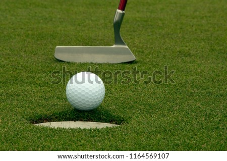 Putter with golf ball entering the cup