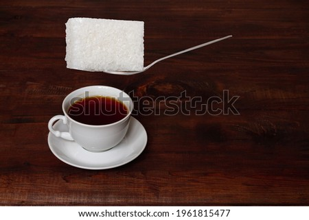 Putting a huge lump of sweet sugar in a cup of tea, the concept of excess, surplus, overabundance, overeating. Foto stock ©