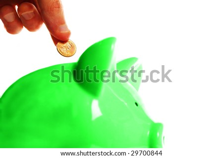 putting a penny in a green piggy bank, on white