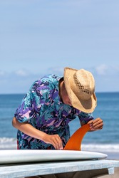 Putting a surfboard fin into a surfboard, the fin is orange in colour and there is an asian boy wearing a Hawaiian shirt and straw hat with red shorts. Chiba, Japan Surfing In Japan, Japan Surf