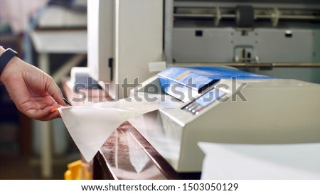 Putting and insert laminating film with paper in laminator. Woman laminating paper in laminating machine in typography hands closeup. Hot and cold lamination machine. Publishing business and industry. Zdjęcia stock ©