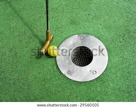 Putting at a mini golf game.