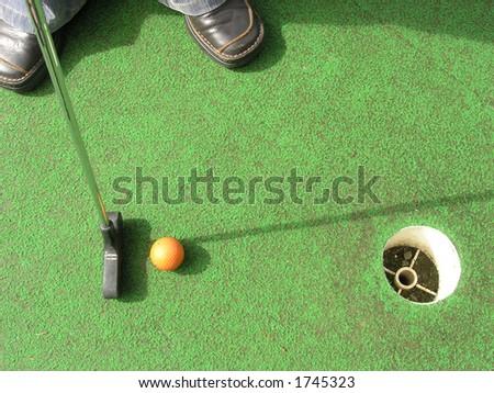 Putting at a mini golf leisure facility.