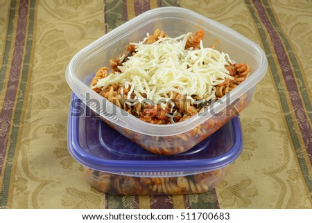 Putting casserole leftovers into plastic containers for work lunches or for freezing with shredded cheese as extra ストックフォト ©