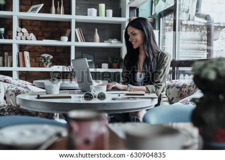 Putting fresh content into her blog. Attractive young smiling woman using laptop while sitting in restaurant