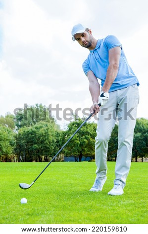 Putting green. Full length of young man in sports clothing playing golf while standing on green