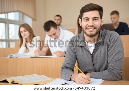 Putting in the effort. Handsome young guy smiling to the camera during the lecture at his university studying in the classroom happiness smart education exam college high school concept copyspace