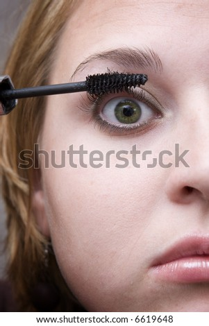 Putting make up on. - stock photo