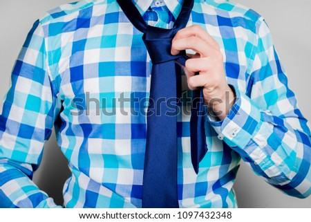 Putting on and tying a tie. The man is holding a tie. Instructions for putting on a tie. Preparation for the windsor node. Front view of a man in a blue shirt.