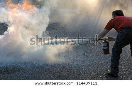 Putting out a fire with a powder type extinguisher.
