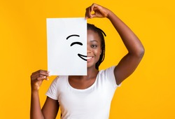 Putting smiling face on. Black girl holding paper with smiley face printed on, happiness and joy concept