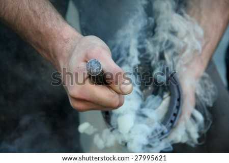 Putting the hot shoe onto the horses hoof - stock photo