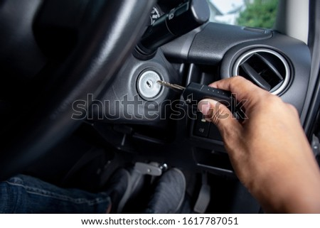 Putting the key into keyhole for ignition the engine. Start the car with key. Foto stock ©