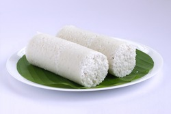 Puttu,steam cake ,white raw rice puttu , pacharisi maavu puttu _breakfast item made using rice flour which is very healthy and arranged in white plate with white background