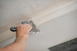 Putty knife in male hand. Hand workю Worker putsty plasterboard ceiling in new appartment. Repairman works with plasterboard, plastering dry-stone wall, home improvement. Man makes repairs at house.