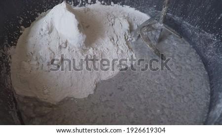 Putty - stir in black bucket. Black bucket with white putty mixture. Building mixture in a bucket. Foto stock ©