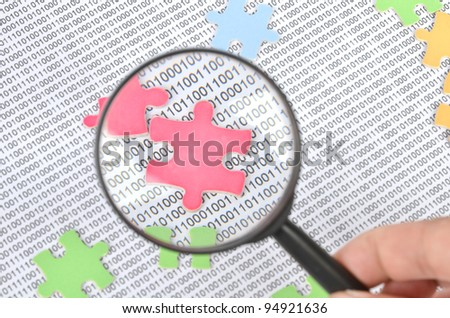 Puzzle and binary code with magnifier - stock photo