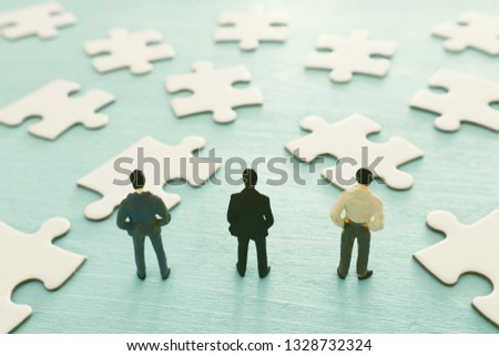 puzzle blocks with miniature people over wooden table ,human resources, problem solving and management concept