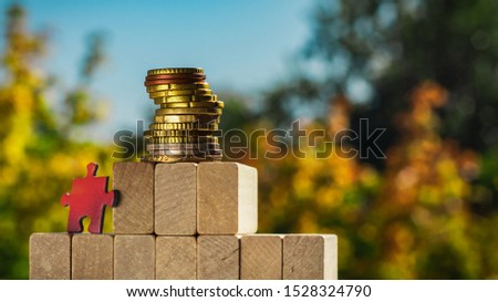 Puzzle climbs to the top of the pyramid made of wooden blocks. The concept of achieving business goals and reaching new levels of promotion.