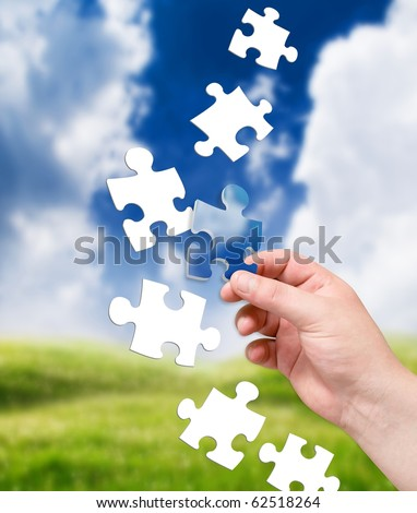 puzzle in hand on landscape background - stock photo