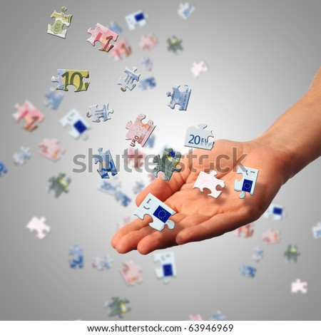 Puzzle of the euro banknotes and hands which it is collected. Symbol of business