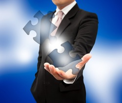 Puzzle on the businessman hands.