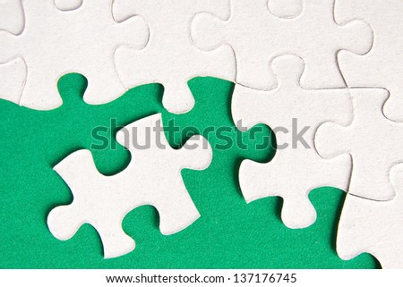 Puzzle pieces on green background close up.