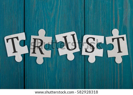 "Puzzle pieces with word ""Trust"" on blue wooden background #582928318"