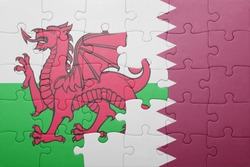 puzzle with the national flag of wales and qatar . concept