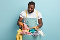 Puzzled Afro American man overstained with housekeeping, does laundry at home during Saturday, looks frustratedly at towel, notices stain, dissatisfied with wash, wears t shirt and blue apron