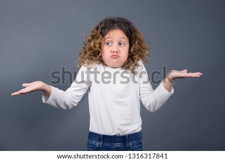 Puzzled and clueless little girl with arms out, shrugging her shoulders, saying: who cares, so what, I don't know. Negative human emotions, facial expressions, life perception and attitude