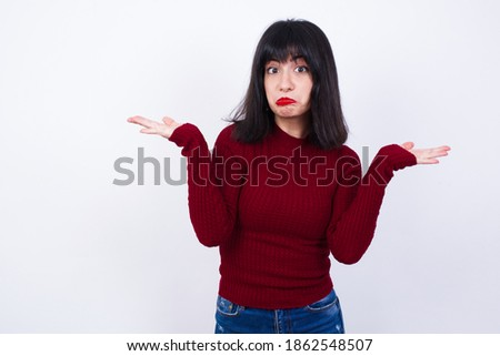 Puzzled and clueless Young Caucasian beautiful woman wearing red T-shirt against white background with arms out, shrugging shoulders, saying: who cares, so what, I don't know. Сток-фото ©