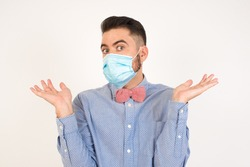 Puzzled and clueless young man wearing medical mask, shrugging his shoulders, saying: who cares, so what, I don't know. Negative human emotions, facial expressions, life perception and attitude