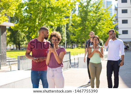 Puzzled and focused people consulting location app to find their way in town. Men and women standing in residential area and using smartphones. Using phones outside concept