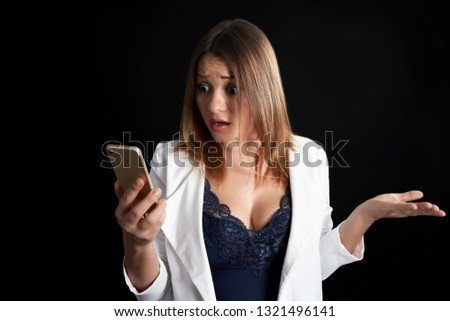Puzzled beautiful businesswoman looking at smartphone. Confused young woman with a quizzical expression, over black background - gesturing and expression, emotion. #1321496141