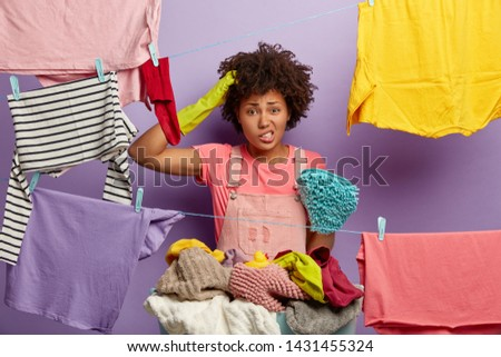 Puzzled beautiful housewife scratches head, feels embarrassed, faces problem, has no powder for washing, does laundry at home, hangs rainbow clothes on rope, stands indoor. Housework concept.