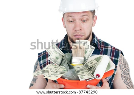 Puzzled brawny repairman with a hardhat full of dollar bills and working instruments