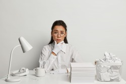Puzzled busy Asian female office worker wears round glasses, white shirt and spectacles, looks sadly, surrounded with pile of paper sheets, desk lamp, headset and cup of drink. Snow white tone