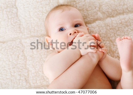 puzzled child with his foot in the mouth - stock photo