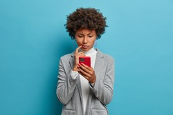 Puzzled confused dark skinned woman in formal wear looks indignant at smartphone, gazes at display, reads business news on website, isolated blue background. People and modern technology concept