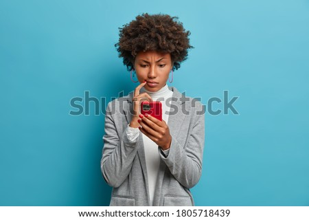 Puzzled confused dark skinned woman in formal wear looks indignant at smartphone, gazes at display, reads business news on website, isolated blue background. People and modern technology concept Foto stock ©