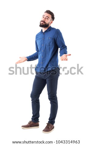 Puzzled confused man in blue shirt shrugging shoulders looking at camera. Full body isolated on white background. #1043314963