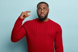 Puzzled dark skinned unshaven man shapes tiny object, tells someone should put little more effort to achieve success, wears spectacles, red jumper, models over blue background. Little thing.
