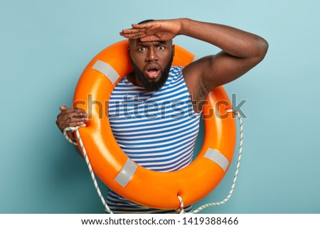 Puzzled discontent Afro American man tries to see something in distance, has frustrated expression, poses with orange inflated lifebuoy, notices emergency situation on summer hot day at ocean or sea #1419388466
