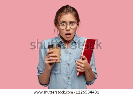 Puzzled emotional student wears spectacles, holds takeaway coffee and red textbook, fails final exam, feels frustrated as didnt enter prestigious university. Negative facial expression. Learning #1226534431