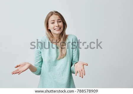 Puzzled female with long blonde hair dressed casually, clenches white teeth in confusion, shrugs shoulders as doesn`t know answer, being clueless and uncertain. Life perception and attitude concept