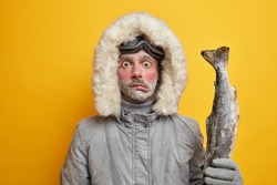Puzzled frozen male fisher has winter expedition in north poses with big fish goes fishing during blizzard or snow storm in arctic place wears outerwear poses over yellow background. Cold frosty day